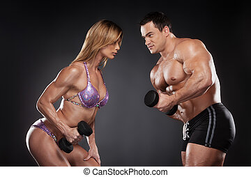 Competition between female and male bodybuilder. Standing...