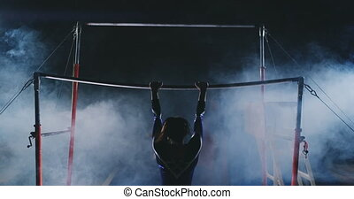 Competitions in gymnastics. A woman walks to the crossbar...