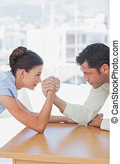 Competitive business people arm wrestling in the office