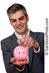Competitive businessman saving money in a piggybank