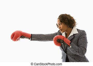 Businesswoman wearing boxing gloves punching.
