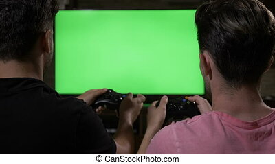 Competitive male friends enjoy playing video games with...