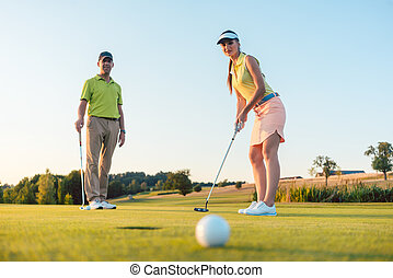 Competitive woman looking at the golf ball with disappointment
