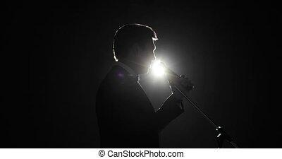 complet, homme parler, spotlight., étape, sombre, microphone, debout, orateur