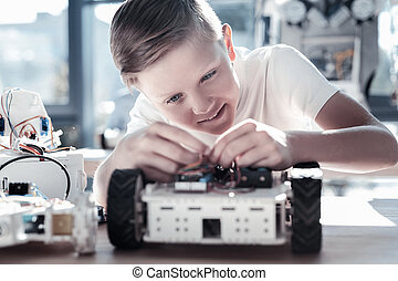 Completely absorbed in process schoolboy designing robot