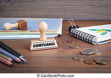 Compliance. Rubber Stamp on desk in the Office
