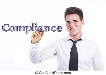 Compliance - Young smiling businessman writing on transparent surface