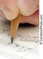 composing musical notes, writing a song with a pencil on paper