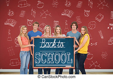 A group of people holding blackboard with message on wooden...