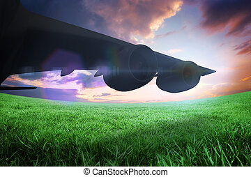 Composite image of airplane cast shadow against green field...