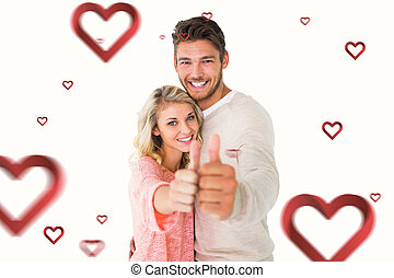 Composite image of attractive couple showing thumbs up to camera