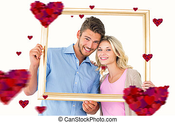 Composite image of attractive young couple holding picture frame