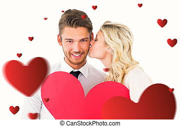 Composite image of attractive young couple holding red heart...