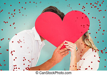Composite image of attractive young couple kissing behind...