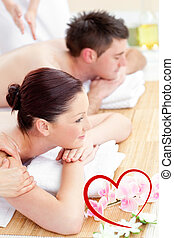 Composite image of attractive young couple enjoying a back massa