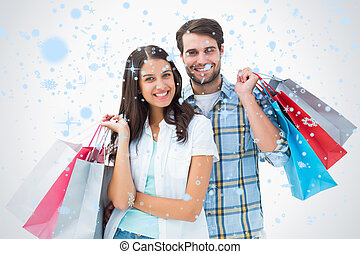 Composite image of attractive young couple with shopping bags