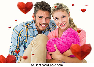 Composite image of attractive young couple sitting holding heart