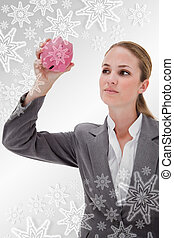 Composite image of bank employee taking close look at piggy bank
