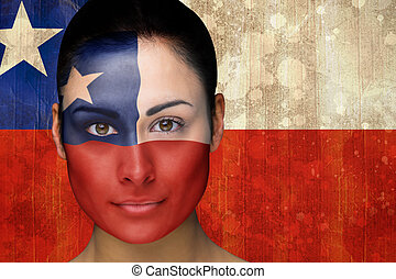 Composite image of beautiful football fan in face paint against chile flag in grunge effect