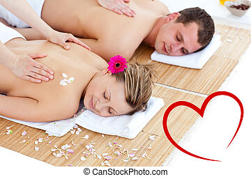 Composite image of beautiful young couple receiving a back massa