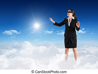 Composite image of blindfolded businesswoman with hands out...