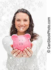 Composite image of brunette showing a piggy bank