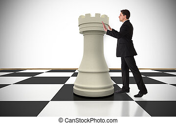 Composite image of businessman in suit pushing chess piece