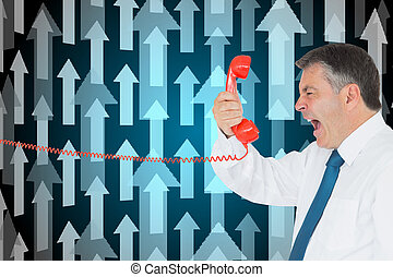 Composite image of businessman screaming directly into the red telephone handset