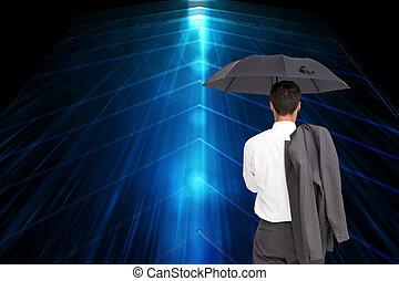Composite image of businessman standing back to camera holding umbrella and jacket on shoulder