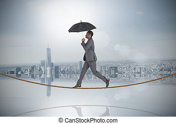 Composite image of businessman walking and holding umbrella...