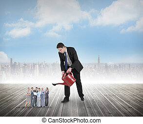 Composite image of businessman watering tiny business team...