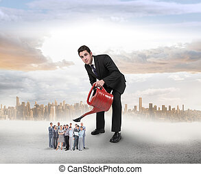 Composite image of businessman watering tiny business team -...