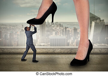 Composite image of businesswoman stepping on tiny ...