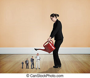 Composite image of businesswoman watering tiny business team