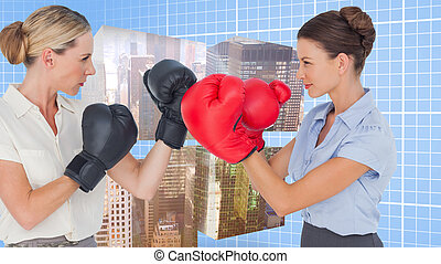 Composite image of businesswomen with boxing gloves fighting