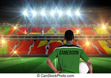 Cameroon football player holding ball against stadium full of cameroon football fans