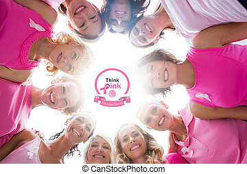 Composite image of cheerful women in circle wearing pink for bre