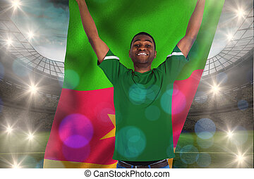 Cheering football fan in green jersey holding cameroon flag against large football stadium with lights
