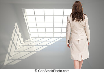 Composite image of classy businesswoman walking away from...
