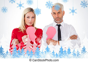 Composite image of couple not talking holding two halves of...