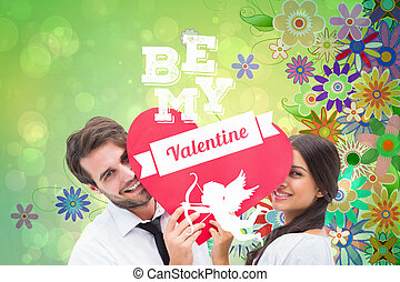 Couple smiling at camera holding a heart against digitally generated girly floral design