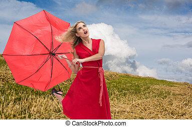 Composite image of elegant blonde holding umbrella -...