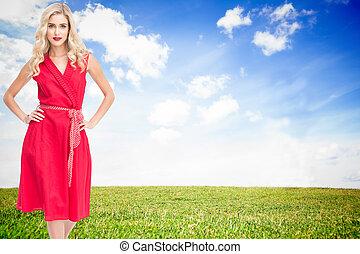 Composite image of elegant blonde standing hands on hips in ...