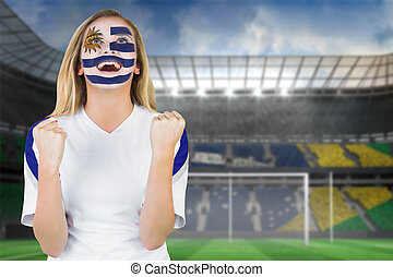 Composite image of excited fan in uruguay face paint...