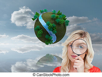 Composite image of fair-haired woman looking through a magnifying glass