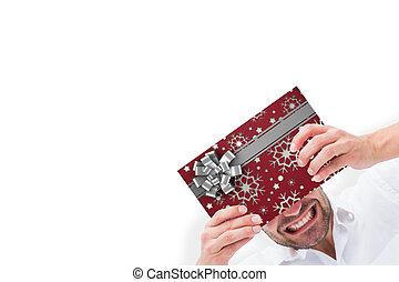 Composite image of festive man holding christmas gift