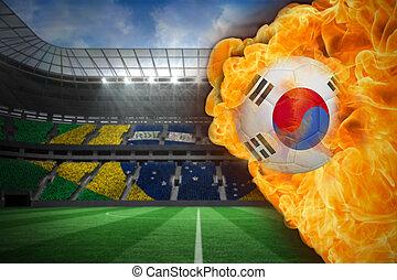 Composite image of fire surrounding korea republic flag football against large football stadium with brasilian fans