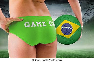 Composite image of fit girl holding brasil ball