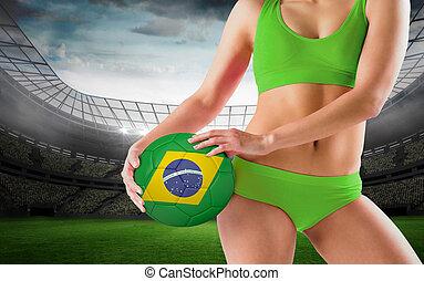 Composite image of fit girl in green bikini holding brasil ball