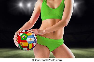 Composite image of fit girl in green bikini holding flag ball